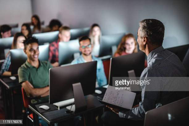 mid adult male teacher teaching the lecture in computer lab. - classroom stock pictures, royalty-free photos & images