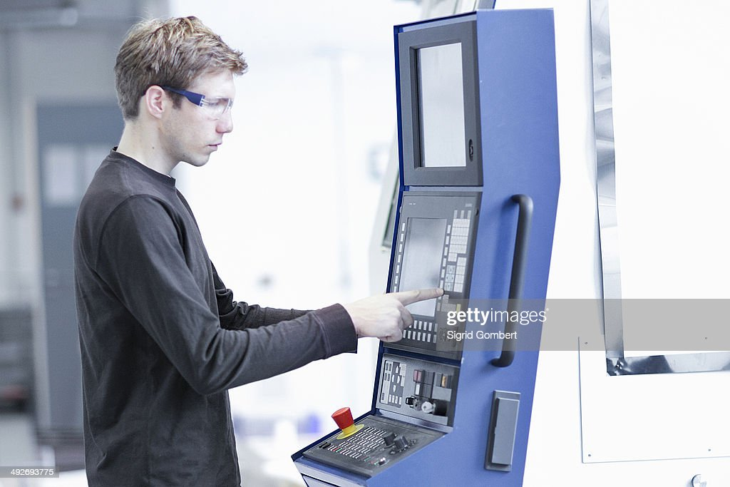 Mid adult male technician maintaining machines in engineering plant : Stock-Foto