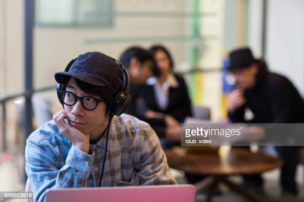 mid adult male working on a computer in a public space - adult video japan stock pictures, royalty-free photos & images
