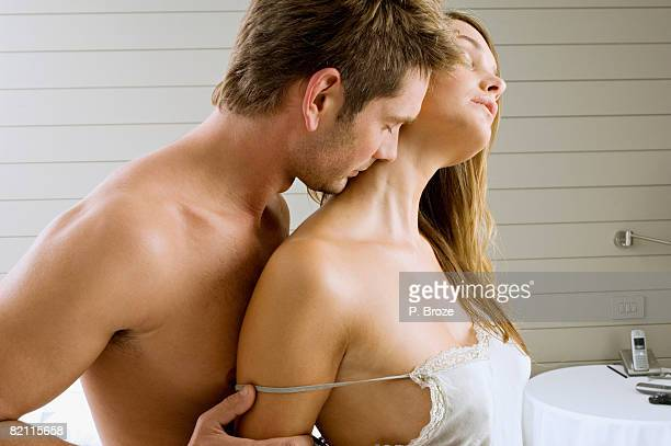 mid adult man and a young woman romancing - couple and kiss and bedroom stock photos and pictures