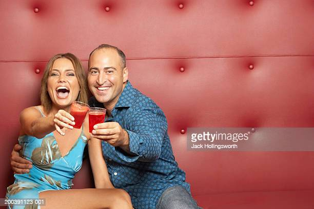 mid adult man and a young woman toasting with glasses - clubkleding stockfoto's en -beelden