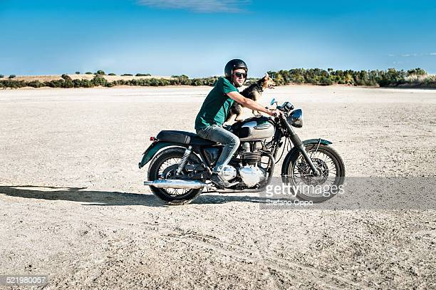 Mid adult man and dog riding motorcycle on arid plain, Cagliari, Sardinia, Italy
