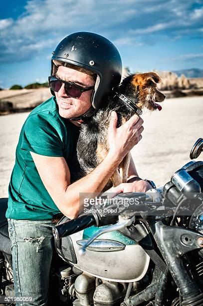 mid adult man and dog sitting on motorcycle on arid plain, cagliari, sardinia, italy - moto humour photos et images de collection