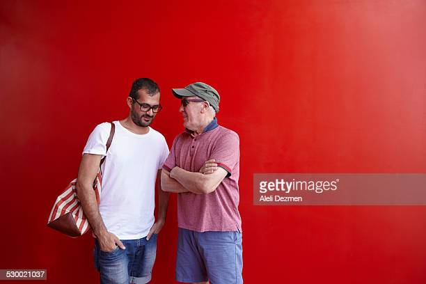 Mid adult man and senior man talking, standing against red background