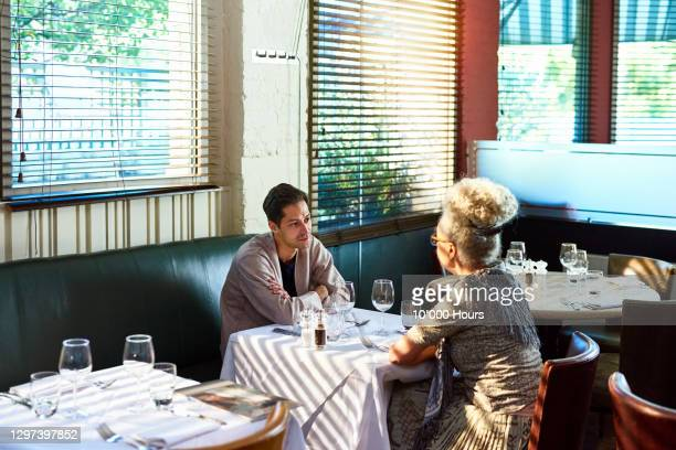 mid adult man and senior woman sitting in restaurant - two people stock pictures, royalty-free photos & images