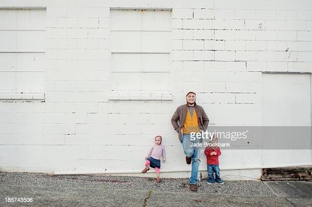 Mid adult man and son and daughter leaning against wall,  portrait