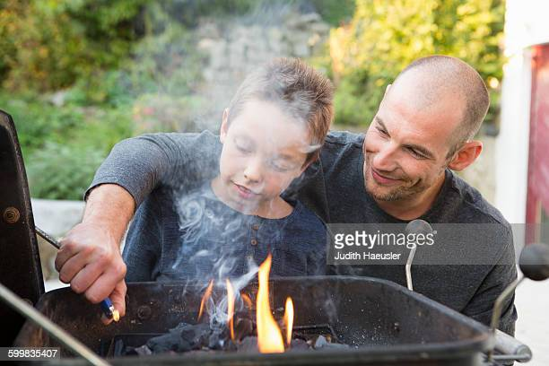 Mid adult man and son lighting barbecue in garden