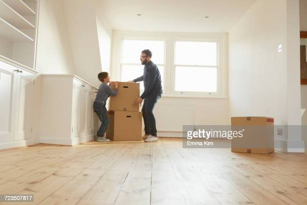 Mid adult man and son stacking cardboard box in new home