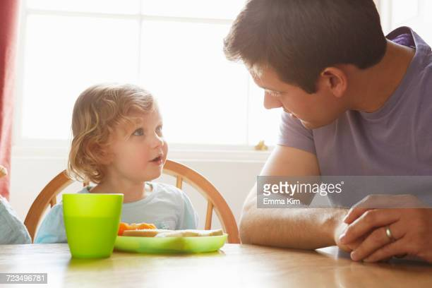 Mid adult man and toddler daughter at kitchen table