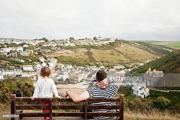 Mid adult man and toddler daughter gazing toward Port Isaac, Cornwall, UK