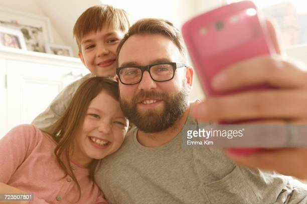 Mid adult man and two children taking smartphone selfie