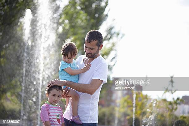 mid adult man and two daughters standing in water fountains, madrid, spain - wet t shirt girls stock photos and pictures