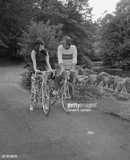 mid adult man and woman cycling on road - {{ collectponotification.cta }} foto e immagini stock