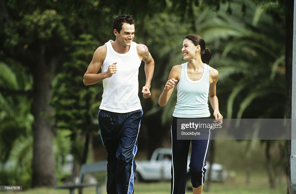 Mid adult man and woman jogging in park,looking in eyes and smiling : Stock Photo