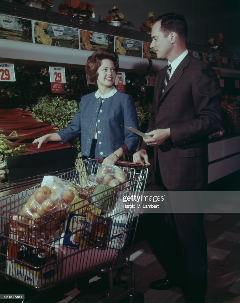 Mid adult man and woman shopping in supermarket with sales clerk in background : Stock Photo