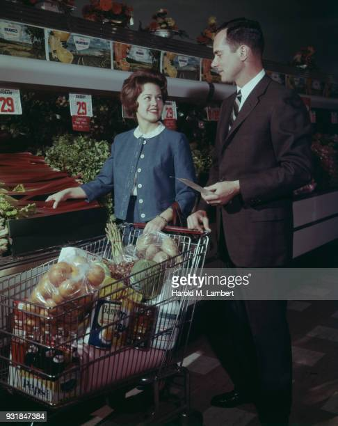 Mid adult man and woman shopping in supermarket with sales clerk in background
