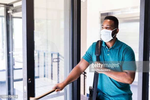 mid adult man arriving at work during covid-19 - arrival stock pictures, royalty-free photos & images