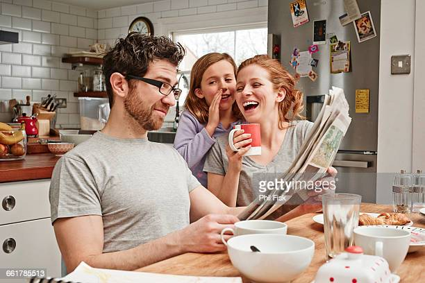 mid adult man at breakfast table reading newspaper whilst daughter and mother laughing - prima colazione foto e immagini stock