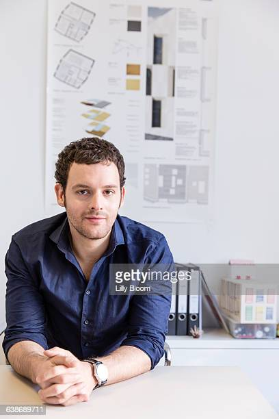 Mid adult man at desk in office in front of blueprint looking at camera