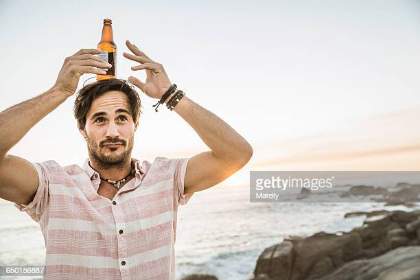 Mid adult man balancing beer bottle on head at beach, Cape Town, South Africa