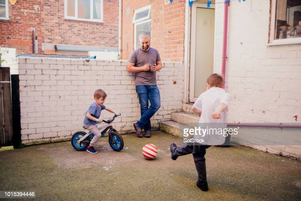 mid adult man bonding with his sons in the yard - one parent stock pictures, royalty-free photos & images