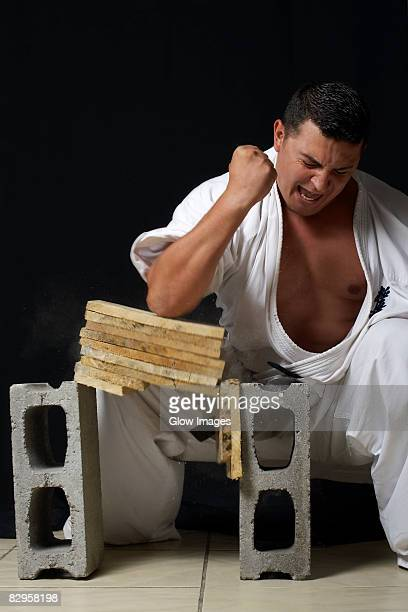 Mid adult man breaking a stack of woods with his elbow