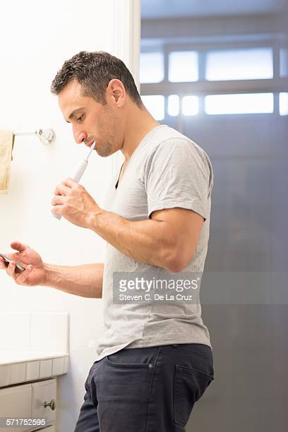 Mid adult man, brushing teeth, looking at mobile phone
