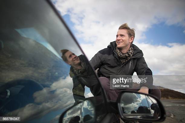 Mid adult man by car looking away, smiling