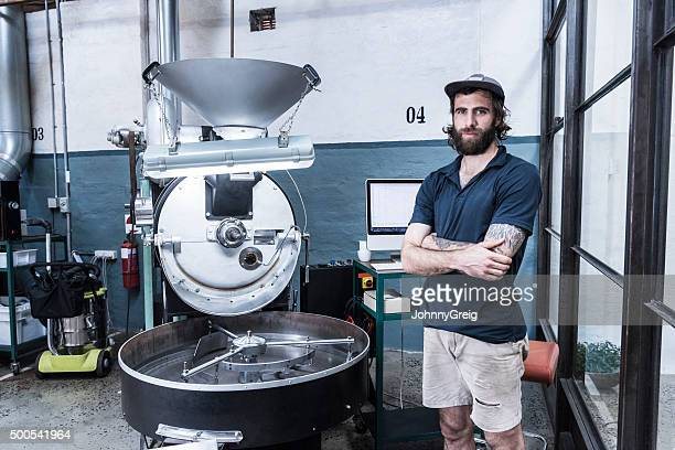 Mid adult man by machinery in coffee roasting warehouse, portrait
