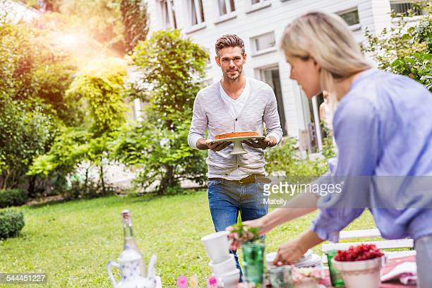 Mid adult man carrying cake on cake stand, walking towards garden table