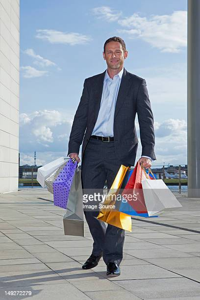 Mid adult man carrying shopping bags