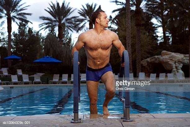 Mid adult man climbing out of swimming pool