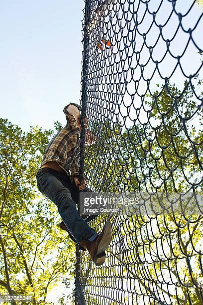 Mid adult man climbing over chain link fence