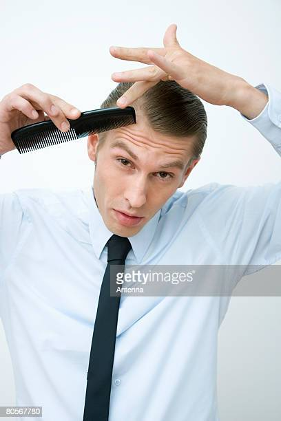 A mid adult man combing his hair