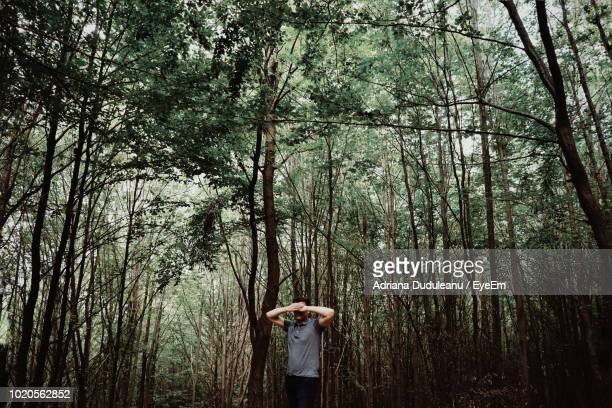 Mid Adult Man Covering Face With Hands While Standing Amidst Trees In Forest