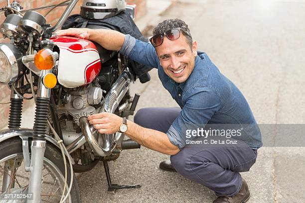 mid adult man crouching beside motorbike - next to stock pictures, royalty-free photos & images