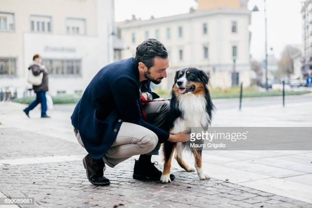 Mid adult man crouching to pet dog in cobbled city square