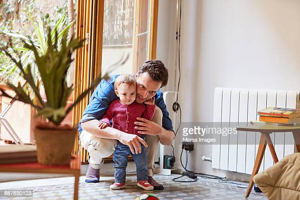 Mid adult man crouching while protecting baby