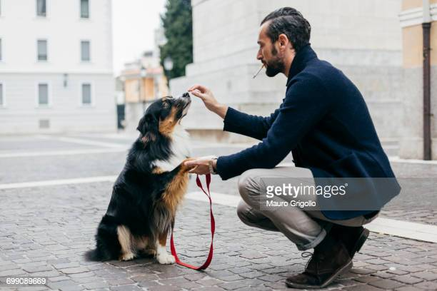 Mid adult man crouching with his dog in cobbled city square