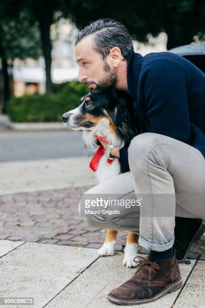 Mid adult man crouching with pet dog on city sidewalk