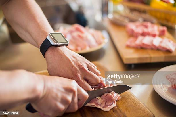 Mid adult man cutting the chicken with a kitchen knife