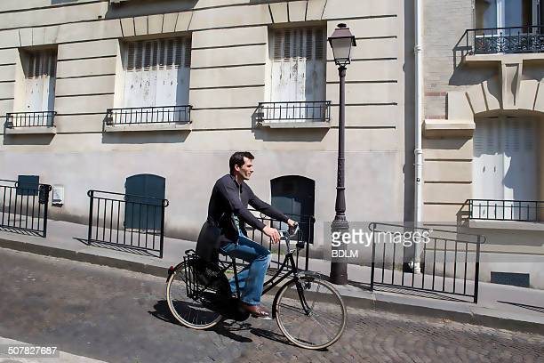 Mid adult man cycling down cobbled city street