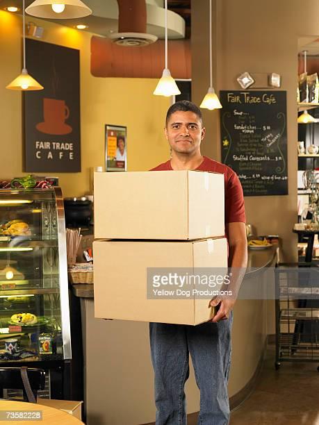 Mid adult man delivering boxes to cafe, portrait