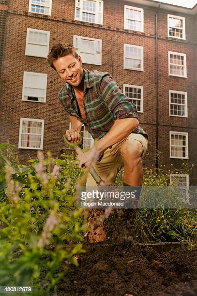 Mid adult man digging on council estate allotment