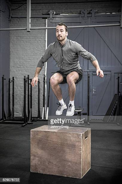 Mid adult man doing box jumps in cross training class