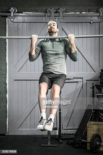 Mid adult man doing chin ups on bar in gym.