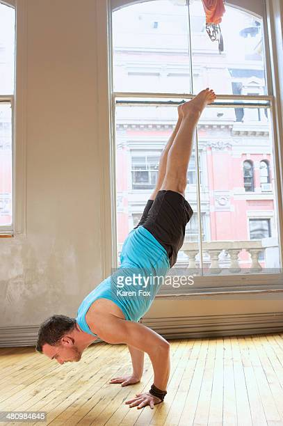 Mid adult man doing handstand