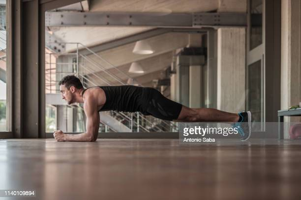 mid adult man doing plank exercise - plank stock pictures, royalty-free photos & images