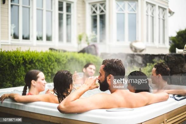 mid adult man drinking alcohol while enjoying with friends in hot tub during weekend - hot tub stock pictures, royalty-free photos & images