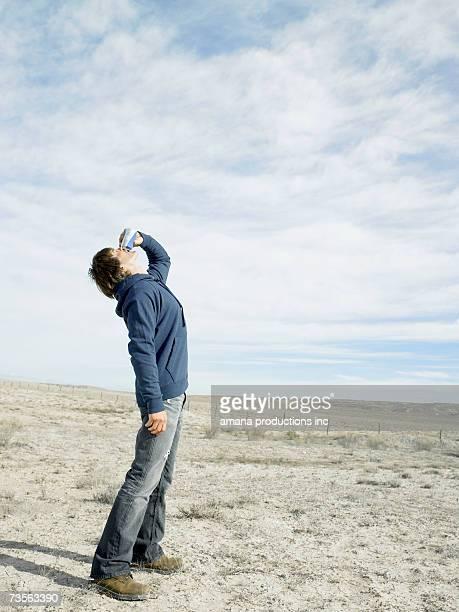 Mid adult man drinking beer in desert